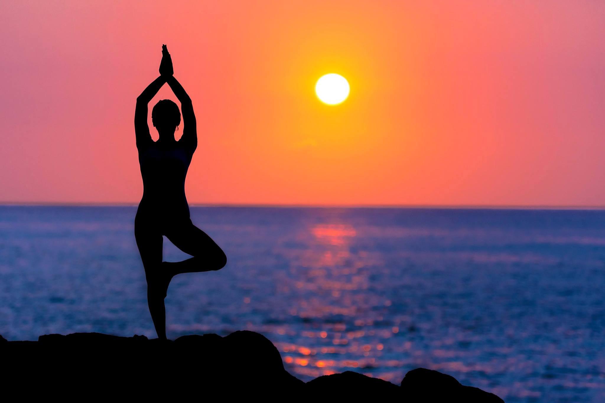 woman-doing-yoga-at-sunset